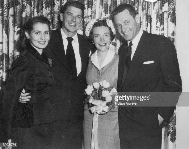 Portrait of American actors Ronald Reagan and Nancy Davis on their wedding day with their arms wrapped around Best Man American actor William Holden...