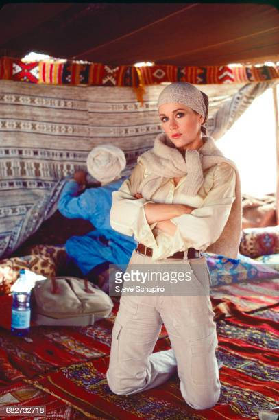 Portrait of American actress Jane Fonda her arms folded as she kneels on a carpet in a tent on the set of the film 'Rollover' Marrakesh Morocco 1981
