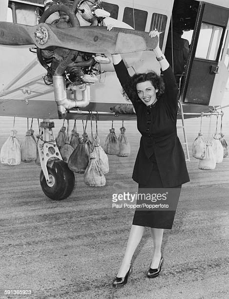 Portrait of American actress Jane Russell star of the Howard Hughes film 'The Outlaw' posing while holding the propeller of a civilian airship used...