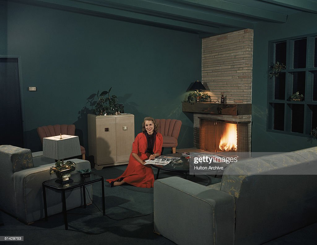 Portrait of American actress Janet Leigh (1927 - 2004) as she sits on the floor of a green living room in a red skirt and jacket and reads a magazine at a coffee table in front of a fire, 1950s.
