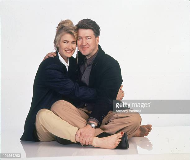 Portrait of American actress Laura Dern and film director David Lynch as they embrace against a white background 1990