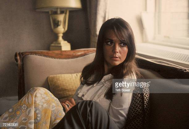 Portrait of American actress Natalie Wood as she sits on a sofa and looks over her shoulder late 1960s