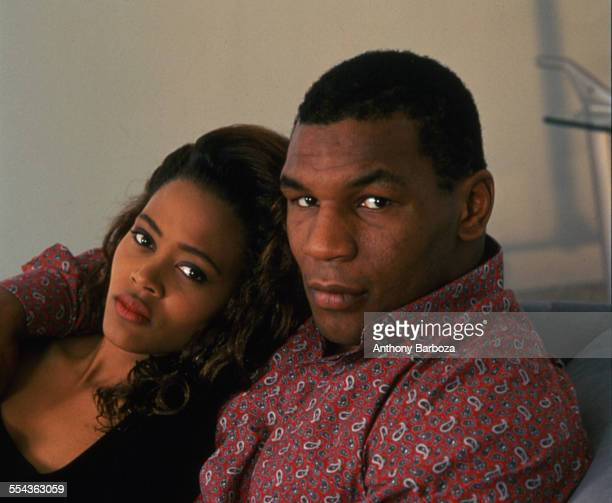 Portrait of American actress Robin Givens and her husband heavyweight boxer Mike Tyson as they sit on a sofa Los Angeles California May 1988