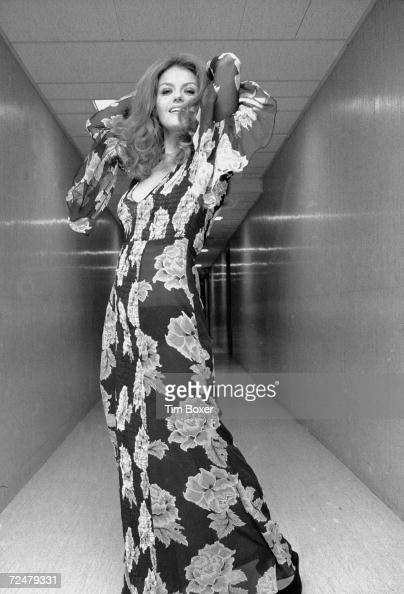 Portrait of American actress Sharon Farrell as she poses in a hallway arms behind her head and wearing a transparent flowerprint dress 1970s