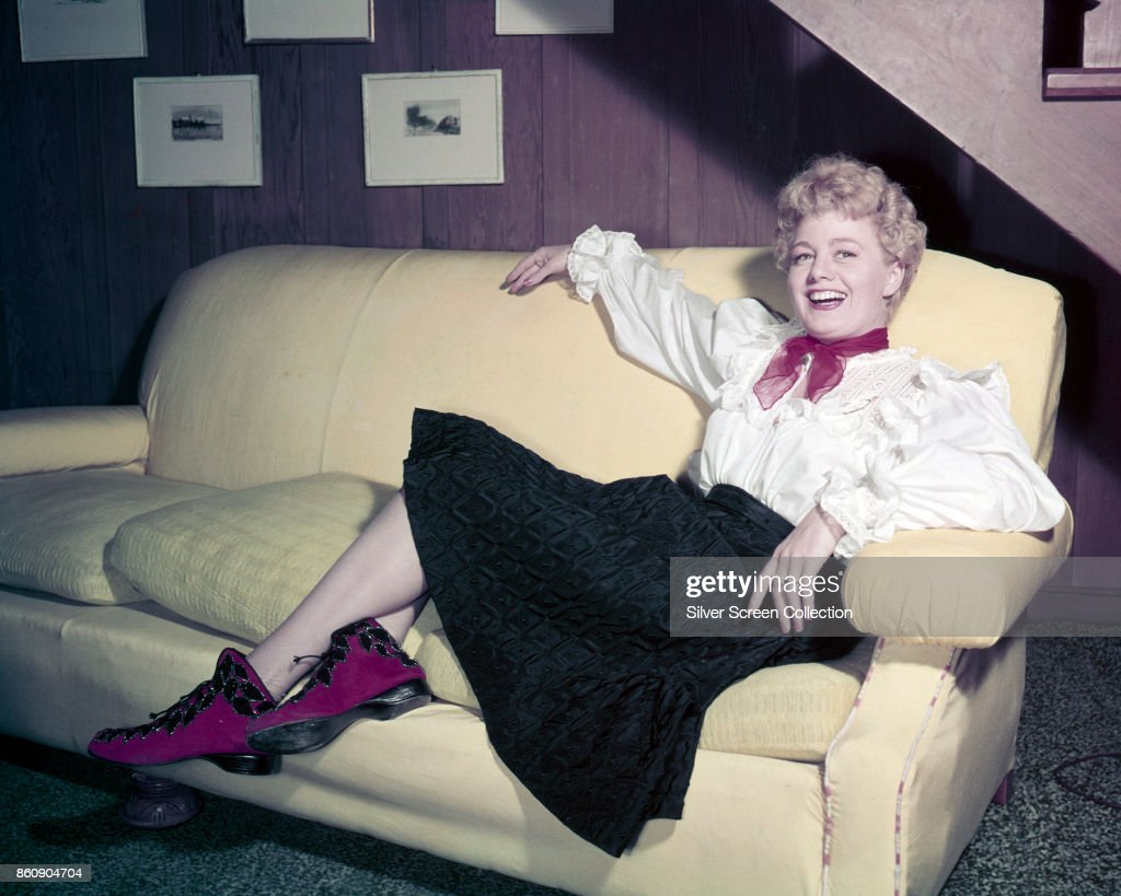 Portrait of American actress Shelley Winters (1920 - 2006) as she laughs, seated on a sofa, 1950s or 1960s. She wears a red scarf, a white blouse with lace and ruffles, a black skirt, and a pair of fuschia boots.