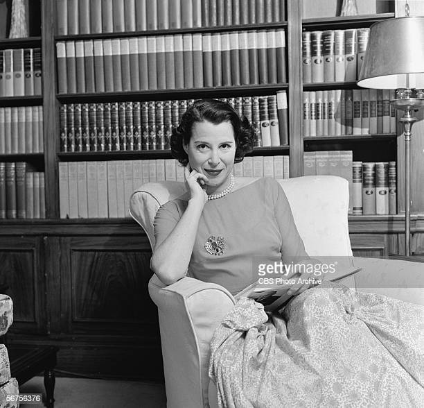 Portrait of American actress socialite and television personality Kitty Carlisle as she sits in an armchair at home an open book in her lap December...