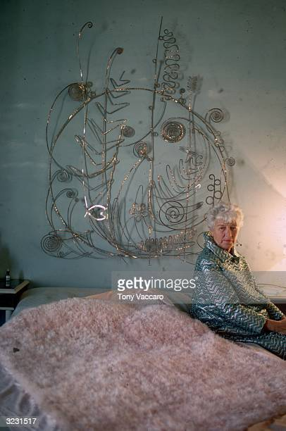 Portrait of American art collector Peggy Guggenheim sitting on her bed in front of the 'Silver Bedhead' sculpture created for her by Alexander Calder...