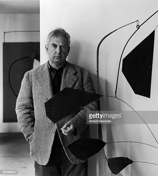 Portrait of American artist Alexander Calder standing beside one of his mobile sculptures New York City September 20 1943