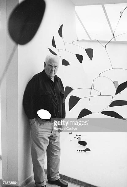 Portrait of American artist and sculptor Alexander Calder as he poses near several of his sculpture mobiles 1970