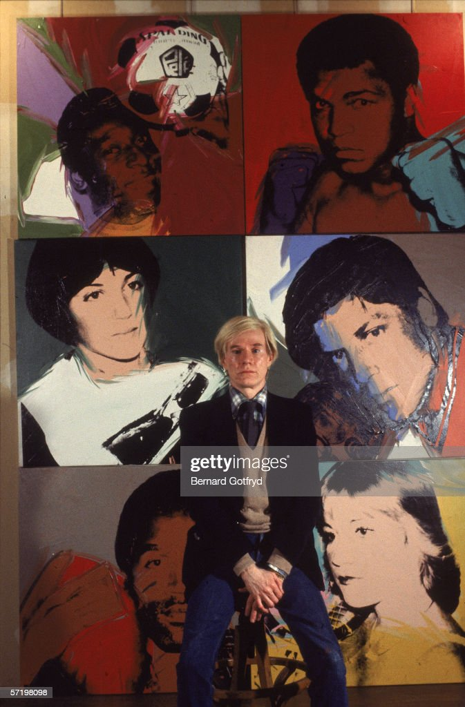 Portrait of American artist <a gi-track='captionPersonalityLinkClicked' href=/galleries/search?phrase=Andy+Warhol&family=editorial&specificpeople=123830 ng-click='$event.stopPropagation()'>Andy Warhol</a> (1928 - 1987) as he sits on a stool in front of six of his lithograph portraits, late 1970s. The paintings behind him, part of his 1979 'Athletes' series show, from left to right, top to bottom, Brazilian soccer player Pele, American boxer Muhammad Ali, American figure skater Dorothy Hamill, American baseball player Tom Seaver, American football player O.J. Simpson, and American tennis player Chris Evert.