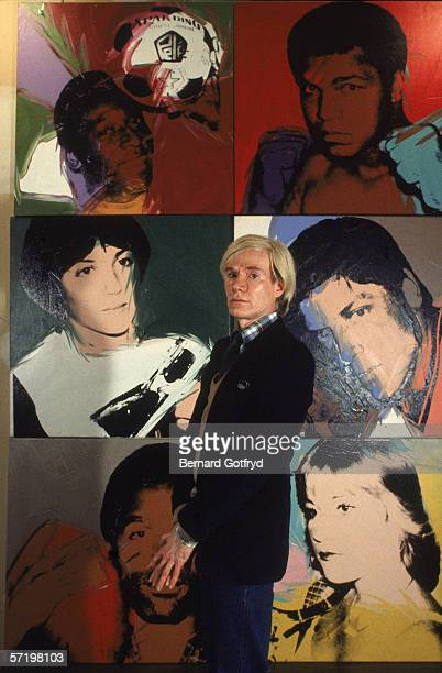 Portrait of American artist Andy Warhol as he stands in front of his six of his lithograph portraits late 1970s The paintings behind him part of his...