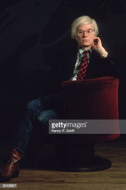 Portrait of American artist Andy Warhol sitting in a red velvet chair against a black background with his hand up to his face He wears a jacket and a...
