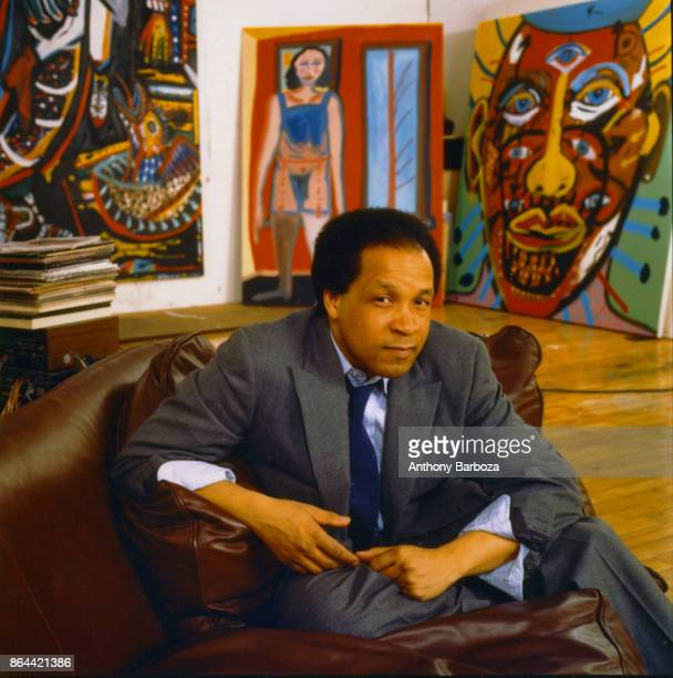 Portrait of American artist Fred Brown as he sits in his studio surrounded by examples of his paintings New York late 1980s