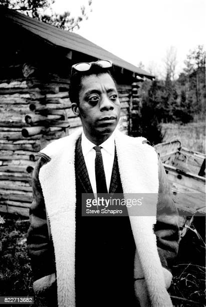 Portrait of American author and activist James Baldwin as he stands outside a log cabin North Carolina 1963