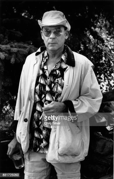 Portrait of American author and journalist Hunter S Thompson as he stands outdoors a cigarette in one hand and a glass in the other Aspen Colorado...