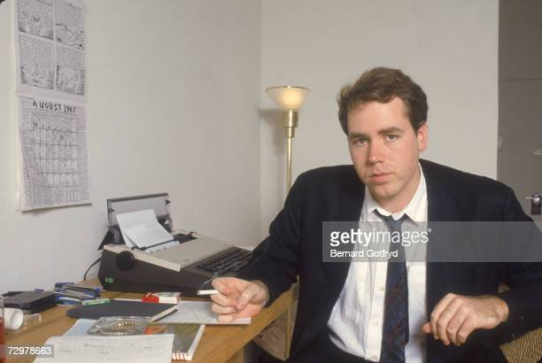 Portrait of American author Bret Easton Ellis as he holds a lit cigarette and sits at a desk dressed in a jacket opencollered shirt and loosened tie...