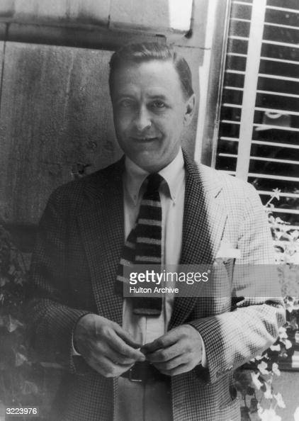 Portrait of American author F Scott Fitzgerald smiling while standing outdoors near a window in jacket and tie Hollywood California