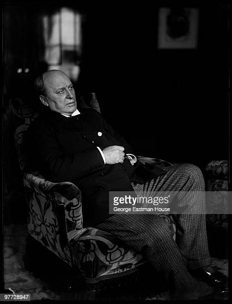 Portrait of American author Henry James as he sits in an armchair early twentieth century