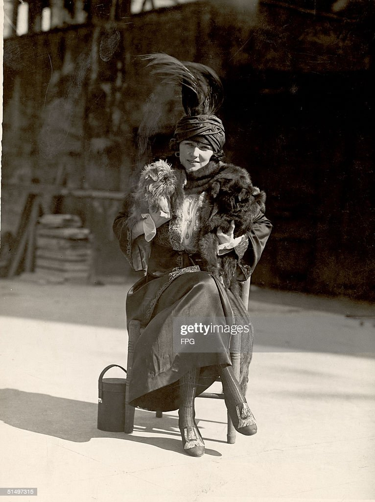 Portrait of American ballroom dancing legend and actress Irene Castle as she sits in a chair outside with her legs crossed and holds her two pet...