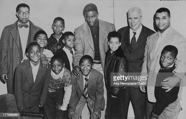Portrait of American baseball player Jackie Robinson of the Brooklyn Dodgers as he poses with teammate Roy Campanella two other men and a group of...