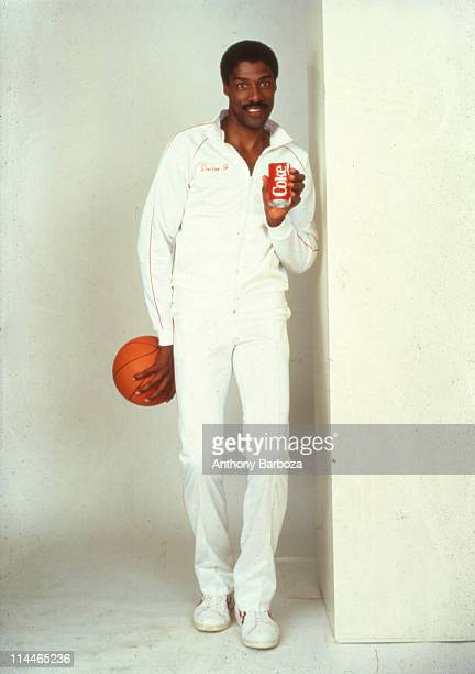 Portrait of American basketball player Julius Irving aslo known as Dr J as he poses with a can of CocaCola in one hand and a basketball in the other...