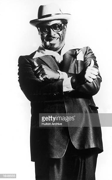 Portrait of American blues guitarist Albert King giving two thumbs with his arms crossed while smoking a pipe 1970s
