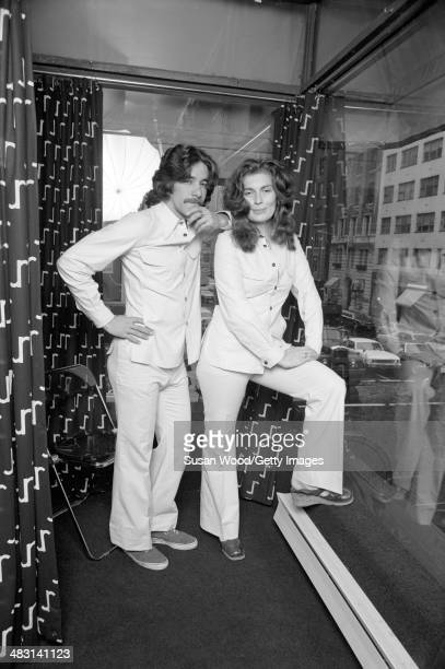 Portrait of American broadcast journalist Geraldo Rivera and fashion designer Jackie Rogers as they pose in matching pantsuits January 1970
