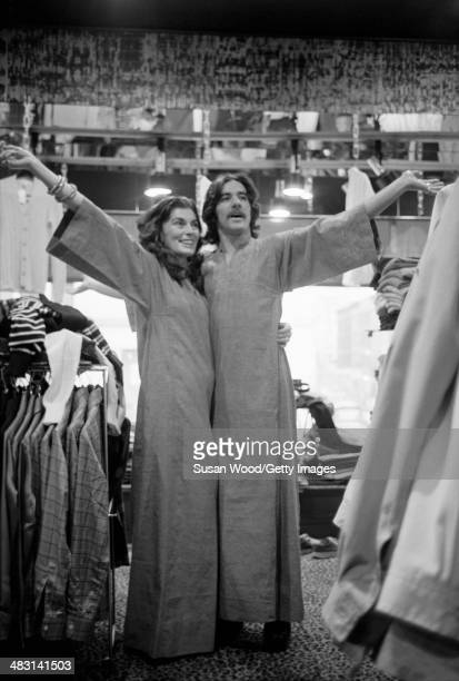 Portrait of American broadcast journalist Geraldo Rivera and fashion designer Jackie Rogers as they pose in matching robes their arms outstretched...