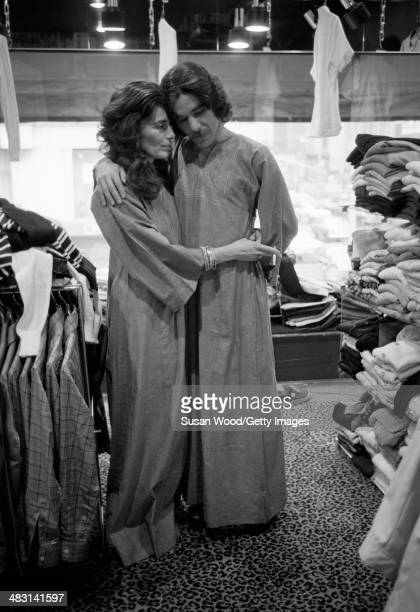 Portrait of American broadcast journalist Geraldo Rivera and fashion designer Jackie Rogers as they pose in matching robes amid racks of clothes...