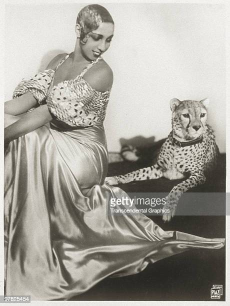 Portrait of American cabaret entertainer Josephine Baker as she sits with her pet cheetah Chiquita early 1930s