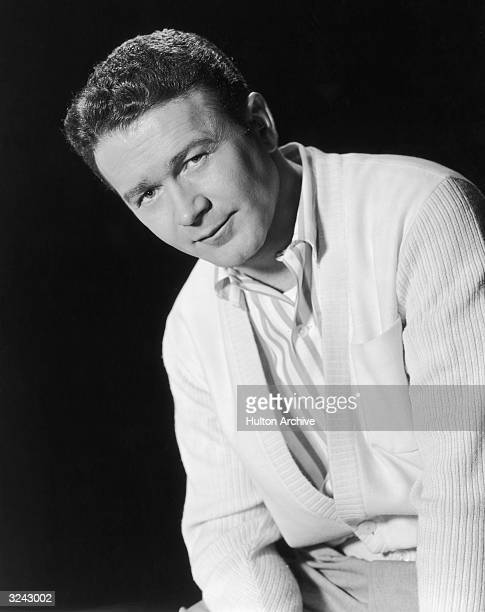 Portrait of American comedian and actor Red Buttons wearing a white cardigan sweater over a striped shirt