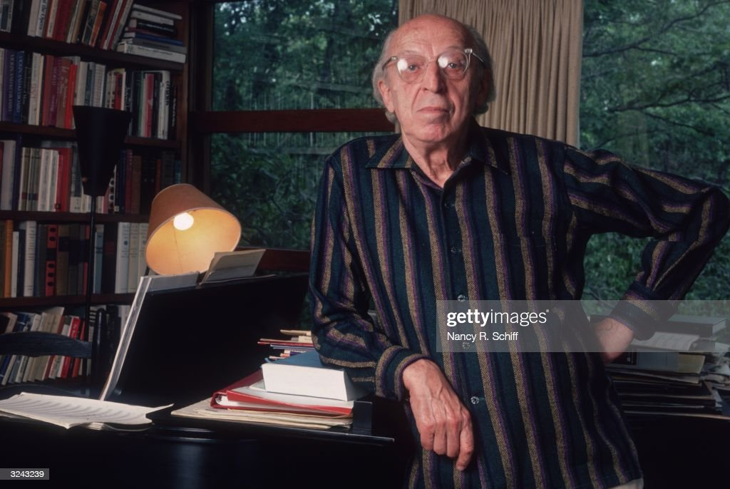 Portrait of American composer <a gi-track='captionPersonalityLinkClicked' href=/galleries/search?phrase=Aaron+Copland&family=editorial&specificpeople=571902 ng-click='$event.stopPropagation()'>Aaron Copland</a> (1900 - 1990), leaning against a piano with one hand on his hip, at his home.