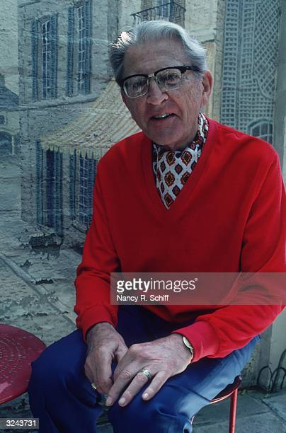 Portrait of American composer Meredith Willson wearing an ascot and a red Vneck sweater sitting in front of a painted mural