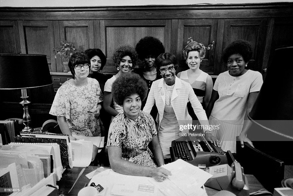 Portrait of American Congresswoman Shirley Chisholm (1924 - 2005) (center right, with one hand on the typewriter) as she poses with her staff in her wood-panelled office, Washington DC, 1970.