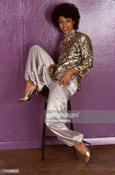 Portrait of American dancer and choreographer Debbie Allen as she poses seated on a stool in front of a purple wall New York New York 1995