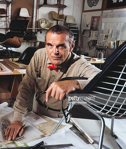 Portrait of American designer Charles Eames as he poses his arm on one of his chairs which sits atop a table in his studio Venice California November...