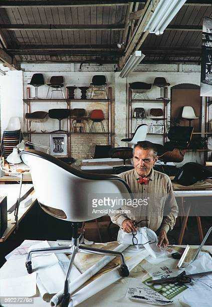 Portrait of American designer Charles Eames in his studio as he stands beside one of his chairs which sits atop a table Venice California November 16...