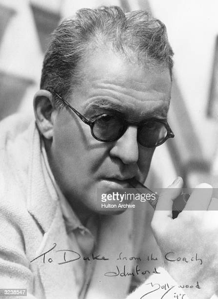 Portrait of American director John Ford wearing sunglasses and smoking a pipe signed 'To Duke from the Coach John Ford' Hollywood California Wayne...