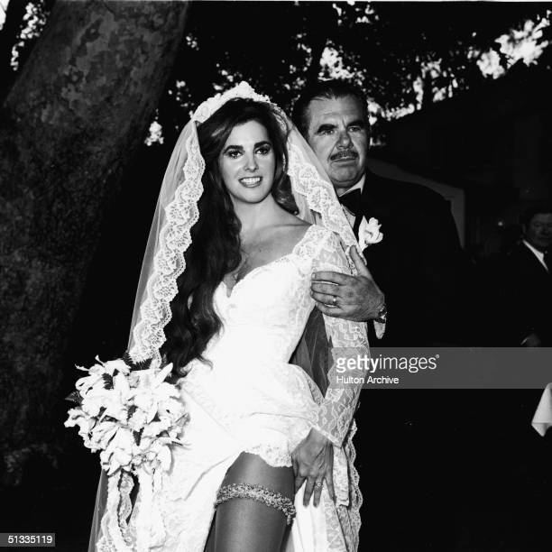 Portrait of American exploitation film director writer producer editor and actor Russ Meyer with his new wife actress Edy Williams as they pose by a...