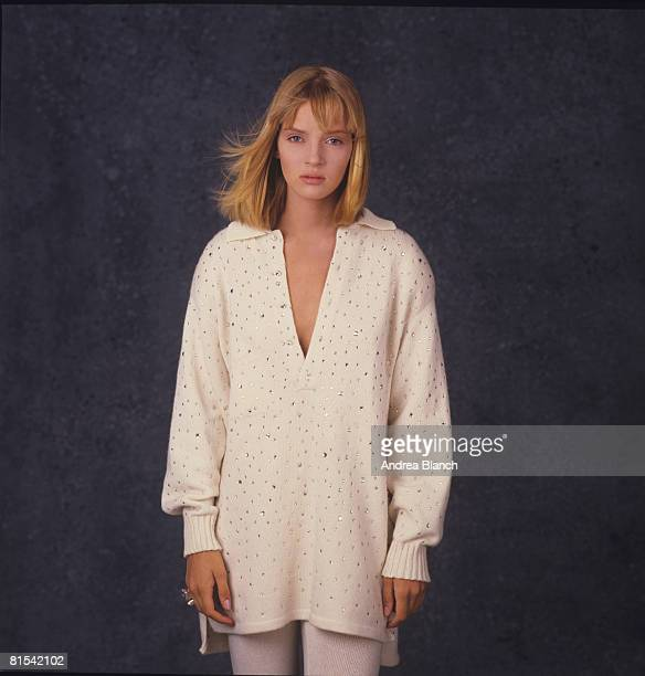 Portrait of American fashion model and film actress Uma Thurman as she poses in front of a blue background for an unidentified magazine photoshoot...