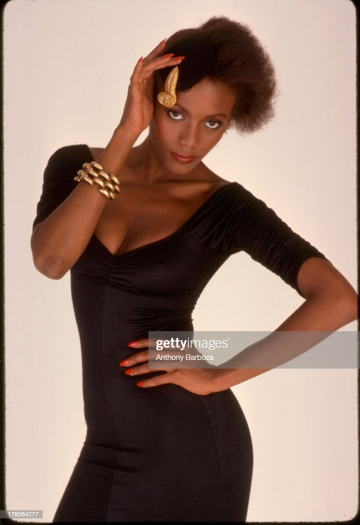 Portrait of American fashion model <a gi-track='captionPersonalityLinkClicked' href=/galleries/search?phrase=Toukie+Smith&family=editorial&specificpeople=1128567 ng-click='$event.stopPropagation()'>Toukie Smith</a> (born Doris Smith) as she poses, one hand on her hip and the other on her hat, against a white background, New York, New York, early 1980s.
