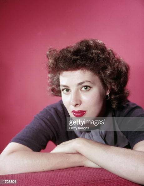 Portrait of American film actor and theater producer Rita Gam against a red background 1950s