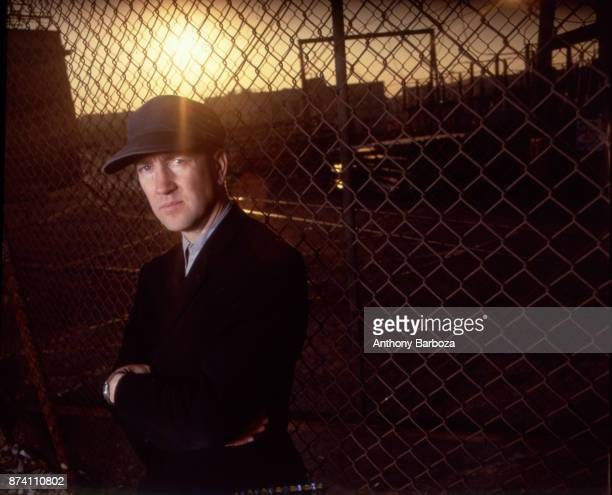 Portrait of American film and television director David Lynch his arms folded as he poses in front of a chainlink fence Los Angeles California 1989