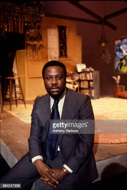 Portrait of American film and theatre producer Woodie King Jr as he poses seated on the front of the set of an unidentified play 1970s 1970s