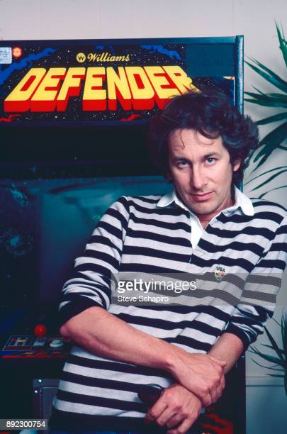 Portrait of American film director Steven Spielberg as he leans leans against an arcade video game Los Angeles California 1981