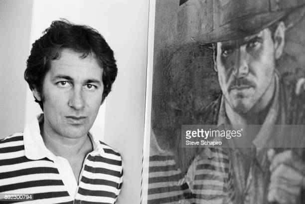 Portrait of American film director Steven Spielberg as he poses beside a framed poster for his film 'Raiders of the Lost Ark' Los Angeles California...