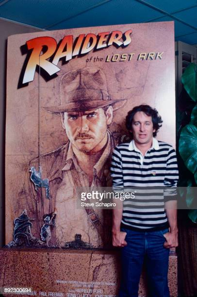 Portrait of American film director Steven Spielberg as he poses with an oversized poster for his film 'Raiders of the Lost Ark' Los Angeles...