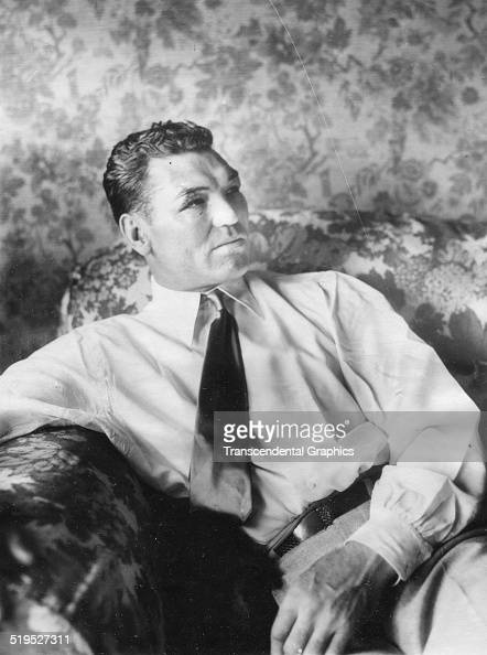 Portrait of American heavyweight boxer Jack Dempsey as he sits in the Flynn House Bronx New York New York July 28 1927 The cuts and bruises on...