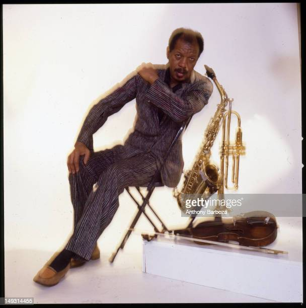 Portrait of American jazz musician and composer Ornette Coleman as he sits in a chair against a white background surround by three of his instruments...