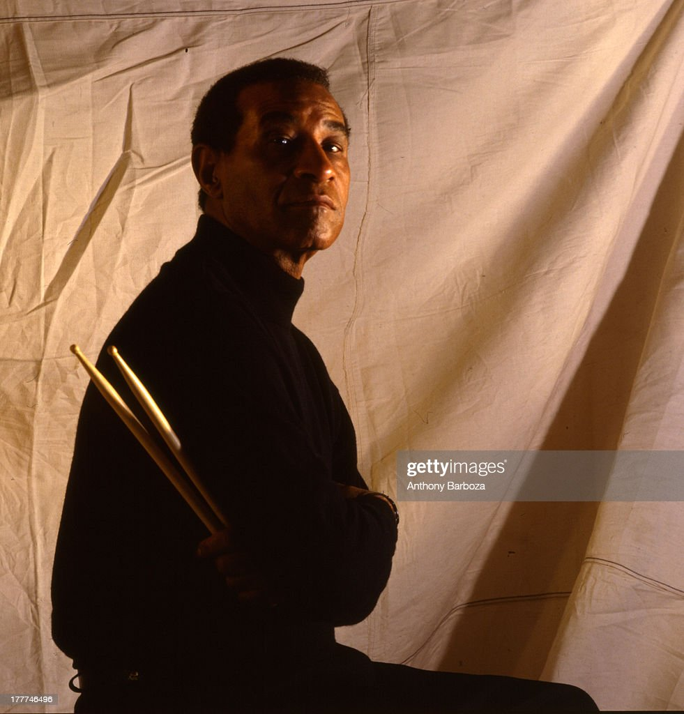 Portrait of American jazz musician Max Roach (1924 - 2007), dressed in a black turtleneck shirt, as he poses against a dropcloth with his drumsticks in his hand, 1989.